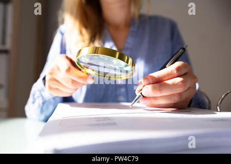 Close-up Of A Businesswoman's Hand Checking Invoice With Magnifying Glass Over Desk - Stock Photo