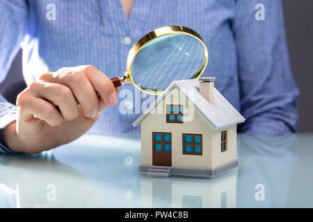 Close-up Of A Businesswoman's Hand Holding Magnifying Glass Over House Model Over Desk - Stock Photo