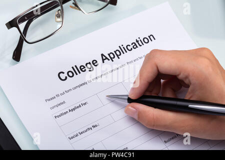Close-up Of A Person's Hand Filling College Application Form With Pen - Stock Photo