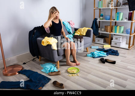 Upset Woman Sitting On Sofa Surrounded By Scatted Clothes - Stock Photo