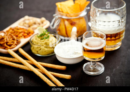 beer and a bowl of guacamole with nachos and salty snacks on an old black wooden table in a pub - Stock Photo