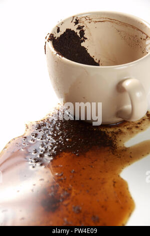 Spilled coffee and coffee grounds on a white background. Cup of coffee with coffee grounds. - Stock Photo