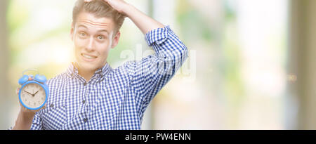 Young handsome blond man holding alarm clock stressed with hand on head, shocked with shame and surprise face, angry and frustrated. Fear and upset fo - Stock Photo