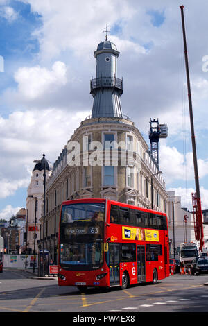 Red Double-Decker Bus in front of the Kings Cross Lighthouse, London - Stock Photo