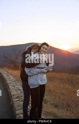 Portrait of happy mother embracing daughter standing on mountain against clear sky during sunset - Stock Photo