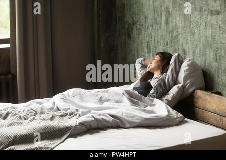 Woman lying and resting in bed on bedroom at home - Stock Photo