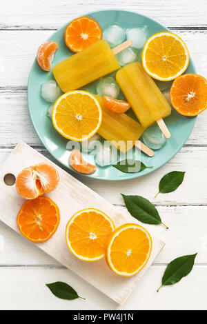 Orange -Tangerine popsicles in blue plate with ice cubes and slices of fruit, white wooden rustic table. Top view, copy space,flat lay - Stock Photo