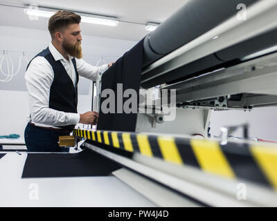 Young bearded tailor working on new clothing design