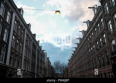 Low angle view of illuminated electric lights hanging amidst buildings against cloudy sky in city - Stock Photo