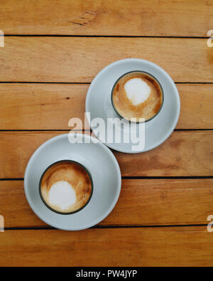 Overhead view of coffee served on wooden table at cafe - Stock Photo