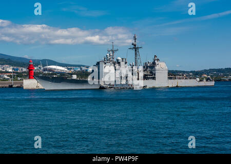 181012-N-TB148-0420 JEJU ISLAND, Republic of Korea, (Oct. 12, 2018) The Ticonderoga-class guided-missile cruiser USS Antietam (CG 54) pulls in to port at the Republic of Korea (ROK) Navy base in Jeju. Antietam is underway with the USS Ronald Reagan (CVN 76) Carrier Strike Group and is forward deployed to the U.S. 7th Fleet area of operations in support of security and stability in the Into-Pacific region.  (U.S. Navy photo by Mass Communication Specialist 3rd Class William Carlisle) - Stock Photo