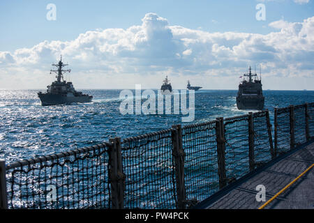 181011-N-TB148-0869 JEJU ISLAND, Republic of Korea, Republic of Korea (Oct. 11, 2018) The guided-missile destroyer USS Benfold (DDG 65), guided-missile cruiser USS Chancellorsville (CG 62) and the forward-deployed nuclear-powered aircraft carrier USS Ronald Reagan (CVN 76) participate in a pass-in-review led by the Republic of Korea Ship (ROKS) Il Chu Bong (LST 688) during the ROK 2018 International Fleet Review (IFR). The IFR is conducted every 10 years and has participants and observers from more than 20 foreign navies. (U.S. Navy photo by Mass Communication Specialist 3rd Class William Carl - Stock Photo