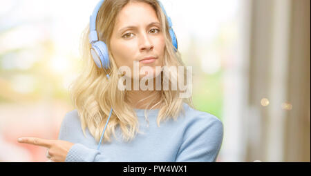 Young beautiful woman listening to music pointing away side with finger - Stock Photo