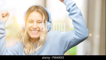 Young beautiful woman listening to music happy and excited celebrating victory expressing big success, power, energy and positive emotions. Celebrates - Stock Photo