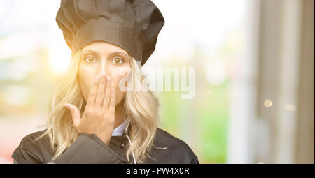 Beautiful cook woman chef covers mouth in shock, looks shy, expressing silence and mistake concepts, scared - Stock Photo