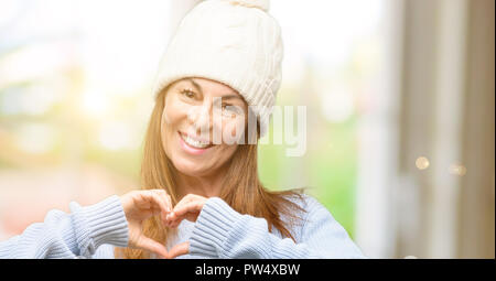 Middle age woman wearing wool winter cap happy showing love with hands in heart shape expressing healthy and marriage symbol - Stock Photo