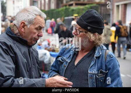 Conversation: two men engaged in a conversation on the street in Amiens, France - Stock Photo