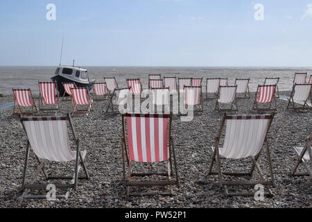 Rows of empty red and white deckchairs on pebble beach with sea and blue sky in background, small blue and white boat on left hand side. - Stock Photo