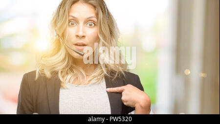 Young woman operator from call center happy and surprised cheering expressing wow gesture, pointing with finger - Stock Photo