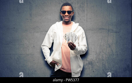 African man holding dollar bank notes confident and happy with a big natural smile laughing - Stock Photo