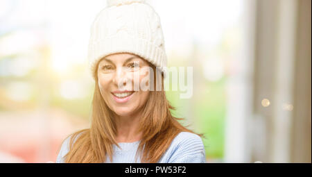 Middle age woman wearing wool winter cap holding something in empty hand - Stock Photo