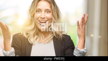 Young woman operator from call center happy and surprised cheering expressing wow gesture - Stock Photo