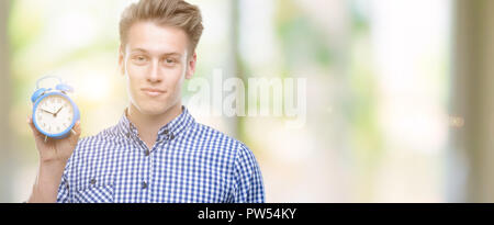Young handsome blond man holding alarm clock with a confident expression on smart face thinking serious - Stock Photo