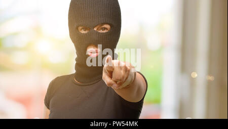 Burglar terrorist woman wearing balaclava ski mask pointing to the front with finger - Stock Photo