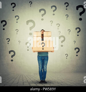 Full length portrait of confused young man carrying heavy packages hidden behind stack of boxes with question marks around. Courier hiding identity of - Stock Photo