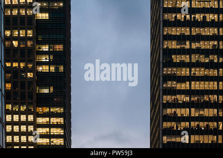 LONDON, UK - NOV 27: Illuminated windows of the skyscrapers of the financial district of Canary Wharf at night in London, UK on November 27, 2013 - Stock Photo