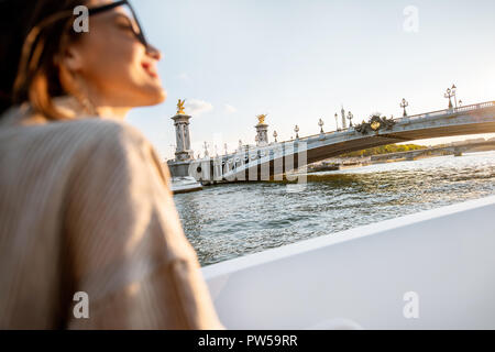 Young woman enjoying beautiful landscape view on the riverside from the ship during the sunset in Paris - Stock Photo
