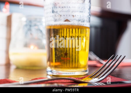 Half drunk glass of lager beer and a fork on a table in a bar - Stock Photo