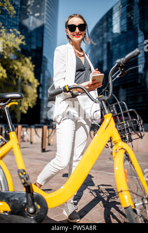 Business woman unlocking public bicycle with smart phone standing at the financial district with skyscrapers on the background - Stock Photo