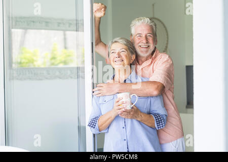happy and beautiful retired couple of man and woman caucasian people enjoying the day together with love and joy at home loooking outside the door win - Stock Photo