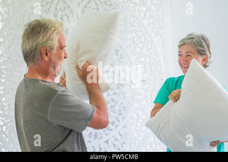 Happy couple of man and woman caucasian people adult senior playing at home in the bedroom with pillow war having a lot of fun with smiles and laugh t - Stock Photo