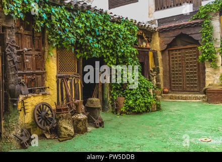 Rural Workshop with many tools used in agriculture: anvil, wheel, animal plough. Baskets, pottery, vines, old shop. - Stock Photo