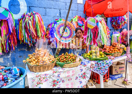 Santiago Sacatepequez, Guatemala - November 1, 2017: Selling fruit & handmade kites in street as crowds head to giant kite festival on All Saints Day. - Stock Photo