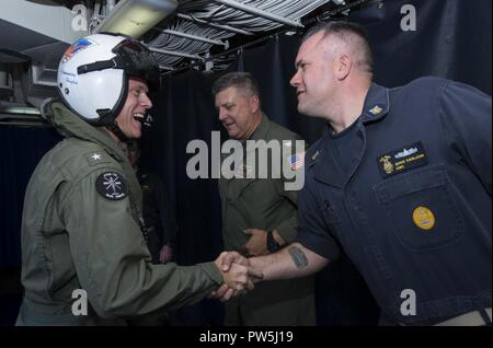 CARIBBEAN SEA (Sept. 19, 2017)  Rear Adm. Jeffrey Hughes, left, commander of Expeditionary Strike Group 2, meets Command Master Chief Gregory Carlson, command master chief of the amphibious assault ship USS Wasp (LHD 1). Wasp is assisting residents of the Caribbean Islands in the wake of Hurricane Irma, and is also preparing to assist once Hurricane Maria makes landfall. - Stock Photo