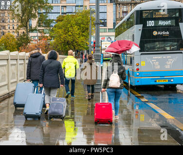 Waverley Bridge, Edinburgh, Scotland, United Kingdom, 12th October 2018. UK Weather: Rain heralds the arrival of Storm Callum in the capital city, but doesn't deter the tourists. The wind breaks a woman's umbrella. Tourists walk in the rain with wheeled suitcases to the airport 100 bus service - Stock Photo