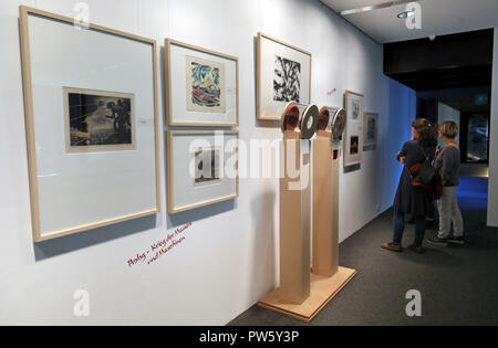 12 October 2018, Mecklenburg-Western Pomerania, Guestrow: 12 October 2018, Germany, Guestrow: Visitors take a look around the Ernst Barlach Foundation in the exhibition 'The Great Small-Format War', which will be officially opened on 13 October 2018. The exhibition, dedicated to the end of the First World War 100 years ago, shows 22 sculptures, 150 graphics and medal art by Ernst Barlach, Rudolf Belling and other artists. Photo: Bernd Wüstneck/dpa - Stock Photo