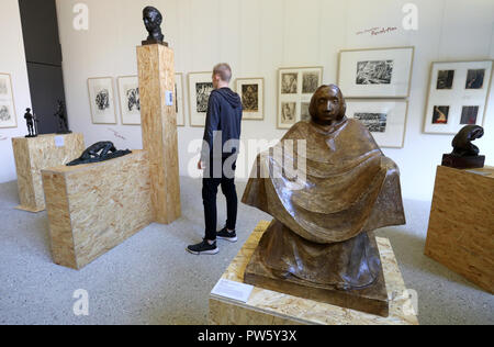 12 October 2018, Mecklenburg-Western Pomerania, Guestrow: 12 October 2018, Germany, Guestrow: A visitor looks around the Ernst Barlach Foundation in the exhibition 'The Great War in Small Format', which will be officially opened on 13 October 2018. The exhibition, dedicated to the end of the First World War 100 years ago, shows 22 sculptures, 150 graphics and medal art by Ernst Barlach, Rudolf Belling and other artists. Photo: Bernd Wüstneck/dpa - Stock Photo