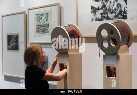 12 October 2018, Mecklenburg-Western Pomerania, Guestrow: 12 October 2018, Germany, Guestrow:Carola Brauer, employee of the Ernst Barlach Foundation, shows how to look at medals in the exhibition 'The Great War in Small Format', which will be officially opened on 13 October 2018. The exhibition, dedicated to the end of the First World War 100 years ago, shows 22 sculptures, 150 graphics and medal art by Ernst Barlach, Rudolf Belling and other artists. Photo: Bernd Wüstneck/dpa - Stock Photo