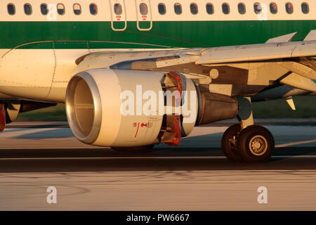 Closeup of a CFM56 turbofan jet engine nacelle on an Airbus A320 airliner while landing with thrust reversers actuated. Left main wheels also visible. - Stock Photo