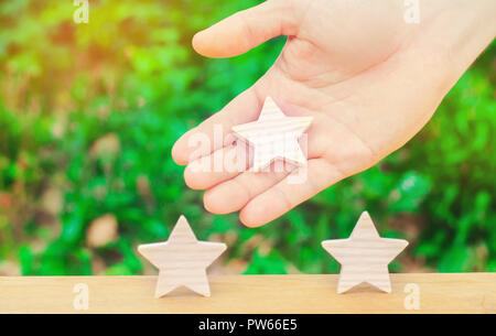 The hand stretches the third star to the other two. The concept of recognition of high quality and good service. Review hotel or cafe. High rating, su - Stock Photo