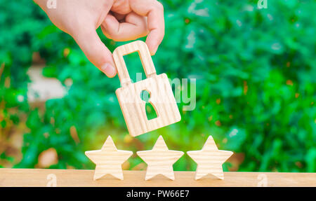Three stars and a hand holding a lock. The concept of high quality and protection. Consolidation of results and achievements. Recognition of quality.  - Stock Photo