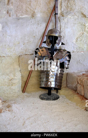 Roman helmet and body armour, displayed against a stone wall - Stock Photo