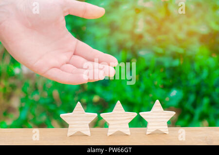 The hand shows the three stasr. The concept of recognition of high quality and good service. Review hotel or cafe. High rating, success and achievemen - Stock Photo