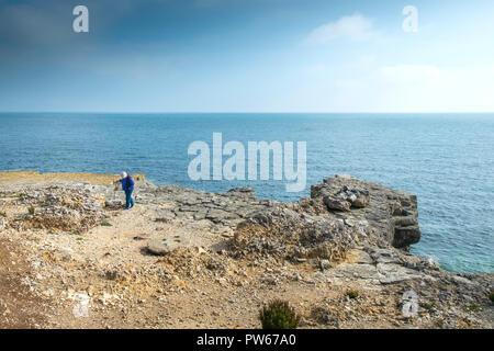A mature woman using a walking stick to walk across rocks on Portland Bill in Dorset in the UK. - Stock Photo