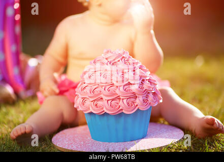 One year old girl eating her first cake - Stock Photo