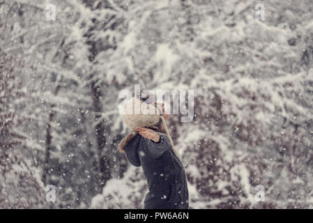 Retro effect faded and toned image of a woman celebrating winter standing outdoors in falling snow with her arms outspread. - Stock Photo